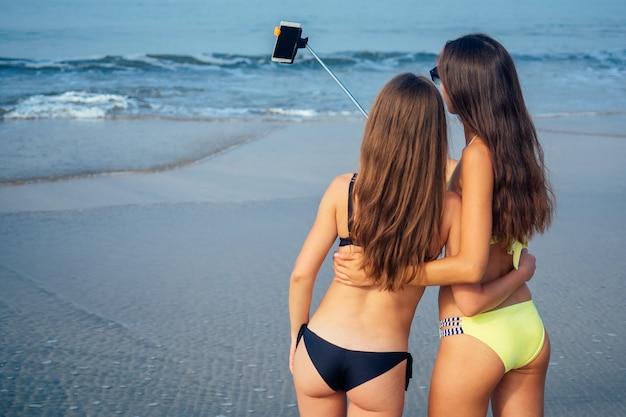 두 명의 아름다운 소녀가 뒤에서 해변 전망의 셀카 스틱에 사진을 찍습니다.