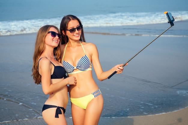2人の美しい女の子がビーチの自撮り棒で写真を撮る