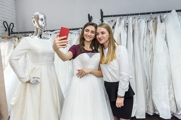 Две красивые девушки делают селфи в свадебном салоне
