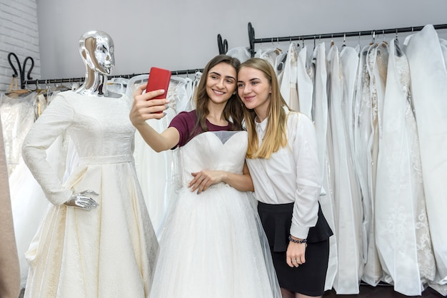 Two beautiful girls making selfie in wedding salon
