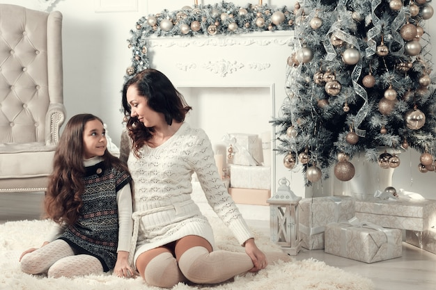 Two beautiful girls, mother and daughter siting on a floor in christmas decorated room.