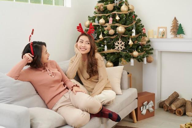 クリスマスツリーの近くで贈り物を待っている2人の美しい女の子