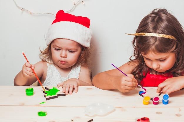 Две красивые девушки расписали деревянные рождественские фигурки