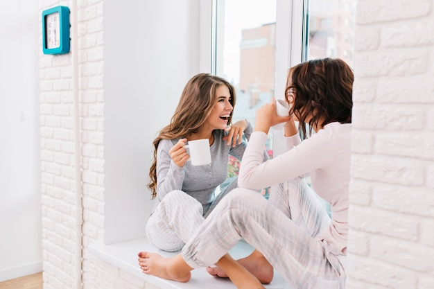 Two beautiful girls in pajamas drinking tea on window in light room. they smiling to each other.