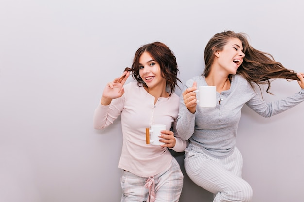 Two beautiful girls in pajamas having fun on gray wall . girl with long hair laughing and keeps eyes closed, other with curly hair smiling .