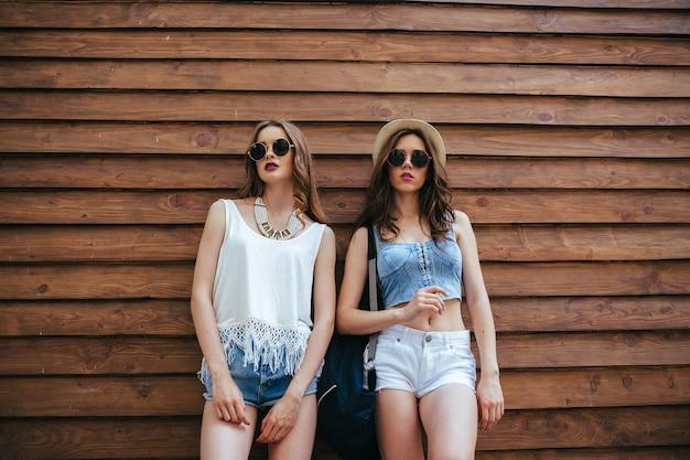 두 명의 아름다운 소녀가 나무 벽 앞에서 포즈를 취합니다.