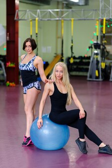 Two beautiful girls posing on the fitball