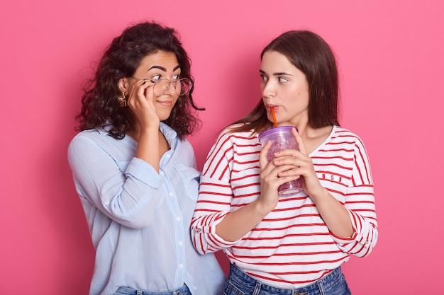 ピンクの壁に対して一緒にポーズをとる2人の美しい女の子