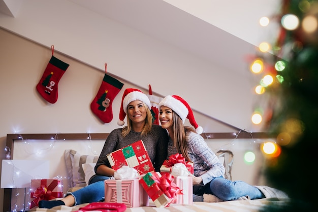 Two beautiful girls sitting on bed with bunch on presents in front of them.