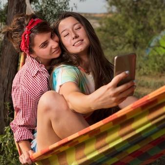 해먹에 앉아있는 두 명의 아름다운 소녀가 추억, 여름 야외 레크리에이션, 개념을위한 셀카를 만듭니다.