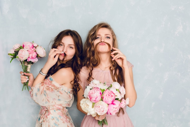 Two beautiful girls stand in a studio, hold bouquets of flowers and play silly.