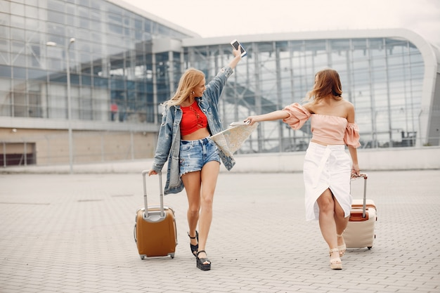 Two beautiful girls standing by the airport
