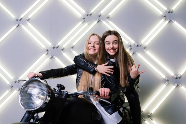 Две красивые девушки в костюмах гонщиков и сидящие на мотоцикле в студии