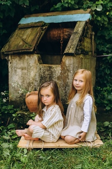 Two beautiful girls in white antique shirts near a well on a background of grass and trees