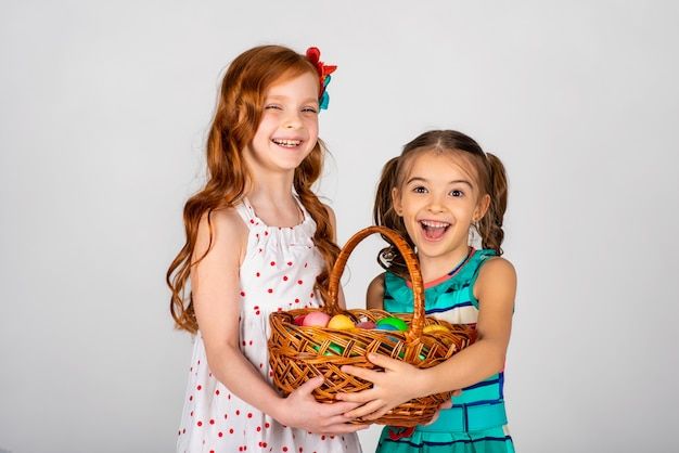 Two beautiful girls on a white background holding a basket with easter eggs and laughing