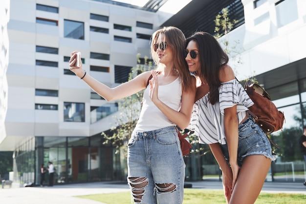 Две красивые девушки с рюкзаками вместе гуляют по городу. довольно милые друзья делятся секретами.