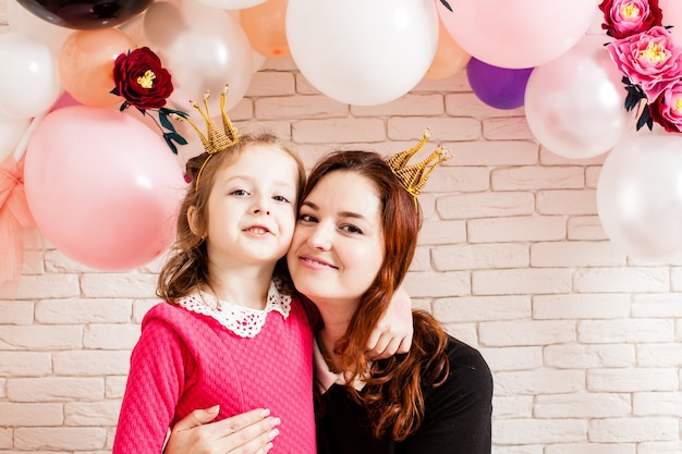 Two beautiful girls with crowns under birthday balloon and paper flower arch decorations. childish photozone for celebration. mom with dauther