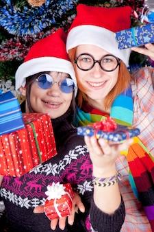クリスマスツリーの近くのクリスマス帽子の贈り物を持つ2人の美しい女の子。