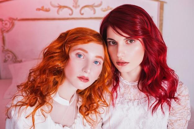美しい白い結婚式のビクトリア朝のドレスに赤い髪の2人の美しい女の子。女性のスタイル。壊れやすい女の子。女性のポートレート。