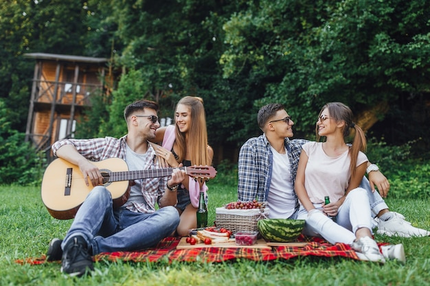 ギターの毛布の上で公園に座っている2人の男の子と2人の美しい女の子、彼らはギターのピクニックとリスニングのメロディーを持っています