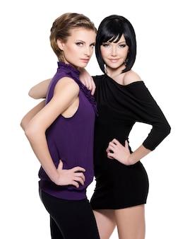 흰색 배경 위에 함께 서있는 두 아름 다운 매력적인 여자