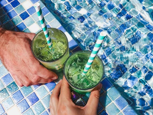 プールの背景にリフレッシュカクテルと2つの美しいグラス。上からの眺め、クローズアップ。休暇と旅行のコンセプト。お祝いの瞬間