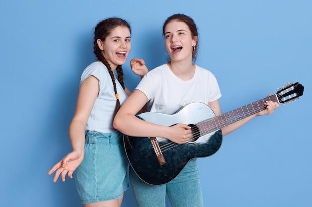2人の美しくゴージャスな愛らしい女性が青い空間で歌を歌ったりギターを弾いたりします