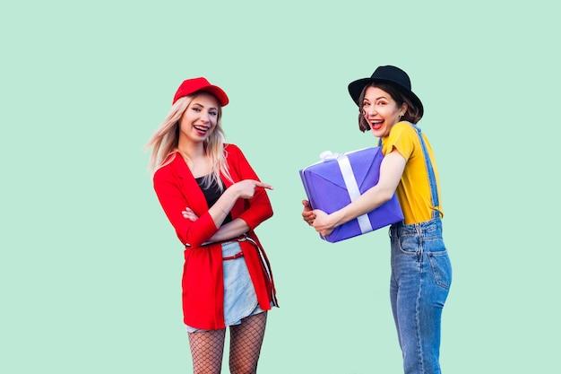 Два красивых счастливых модных хипстера лучшие друзья, счастливая девушка обнимает большую фиолетовую коробку и зубастую улыбку, блондинка, указывая пальцем в настоящее время. студия выстрел, закрытый, изолированные на зеленом фоне