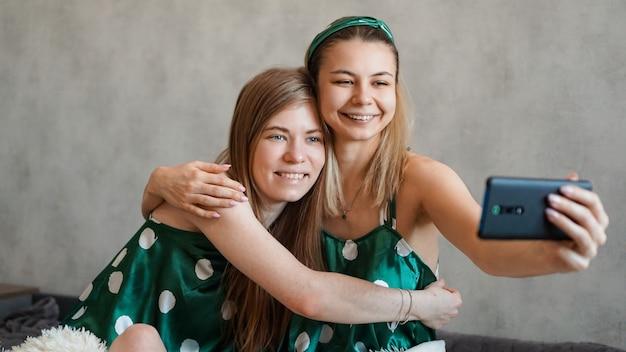 Две красивые счастливые подруги обнимаются и делают селфи со смартфоном на пижамной вечеринке