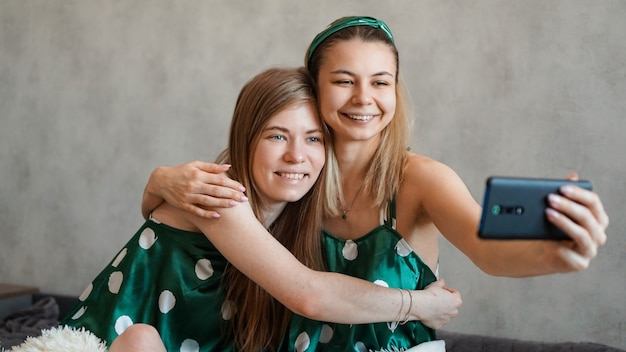 Two beautiful happy girlfriends hugging and taking selfies with smartphone at pajama party