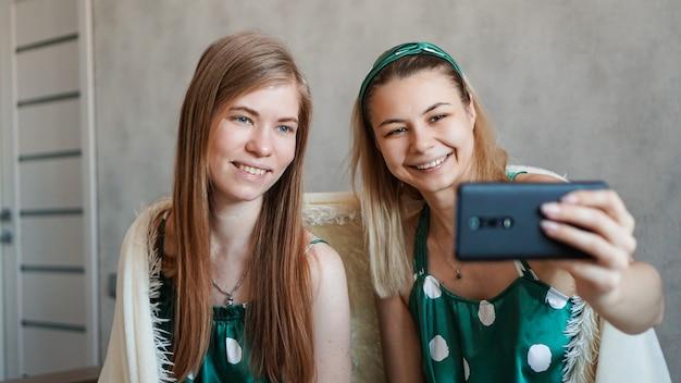 Две красивые счастливые подруги, делающие селфи со смартфоном на пижамной вечеринке