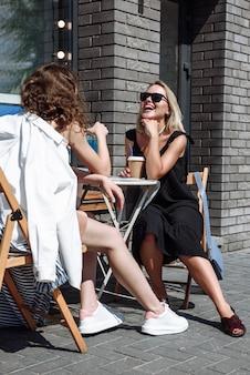 두 명의 아름다운 행복한 여성이 레스토난의 테이블에 앉아서 웃는다
