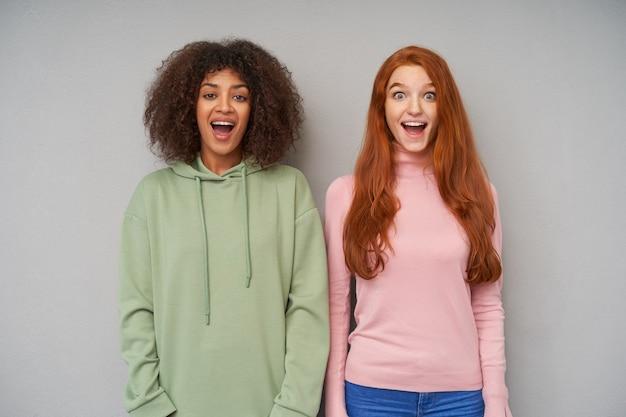 Две красивые радостные барышни, возбужденно смотрящие и с широко открытыми ртами, стоящие над серой стеной с опущенными руками