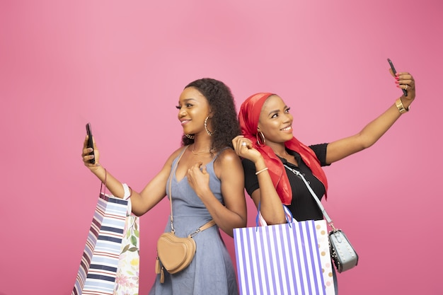 Due belle donne con borse della spesa che si fanno selfie in piedi schiena contro schiena