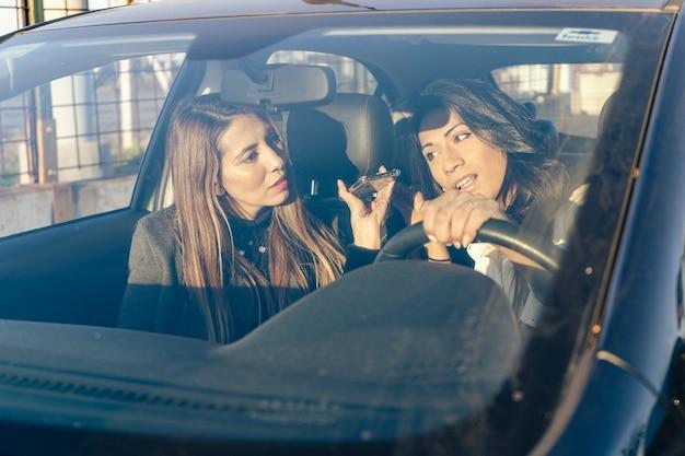 두 명의 아름다운 라틴계 여성이 차 안에서 휴대전화로 메시지를 듣고 있습니다. 통신, 기술, 이동성 개념입니다.