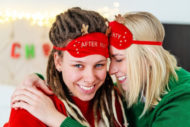 Two beautiful lesbians in sleep masks with deer horns and christmas sweaters hug each other. high quality photo
