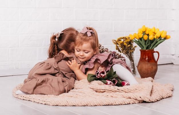 두 아름 다운 어린 소녀 꽃 방에 껴 안고