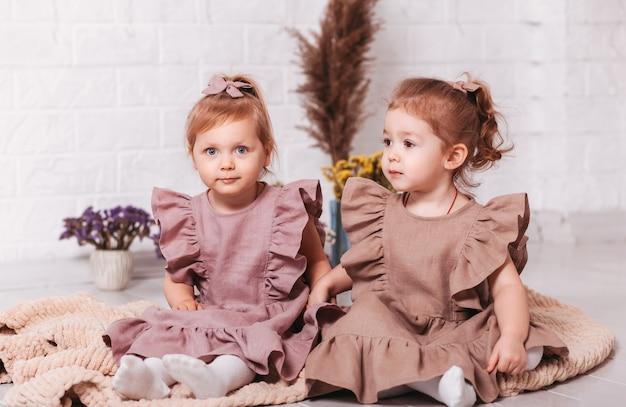 同じドレスを着た2人の美しい少女が隣同士に座っています