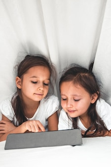 Two beautiful little sisters lying in the bed and look at the screen of a tablet, smart kids using smart technology