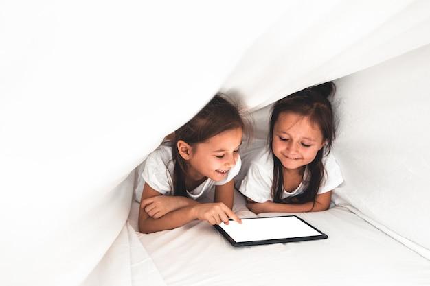 침대에 누워있는 두 명의 아름다운 여동생이 태블릿 화면을보고, 스마트 기술을 사용하는 똑똑한 아이들