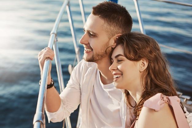 ボートの船首に座って手すりを握りながら大きく笑みを浮かべて恋をする二人の美しい既婚者関係にある若い大人のカップルが彼らのexeについての話を共有します。