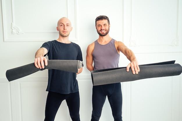 요가를 연습하고 스튜디오에서 즐거운 시간을 보내는 두 명의 아름다운 남자. 요가 수업에서 명상과 지원 그룹. 요가, 친구. 요가 매트 흰색 배경으로 체육관에서 포즈를 취하는 잘 생긴 남성