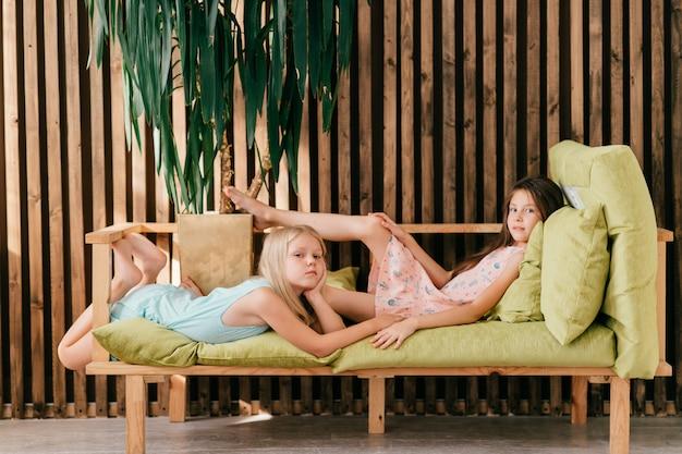インテリアスタジオのベッドの上に横たわると、カメラにポーズをとって2つの美しいモデルgirlsinカラフルなドレス