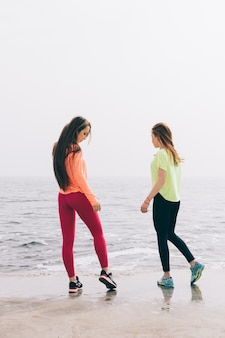Two beautiful muscular young women in sports clothes standing on the beach in the morning