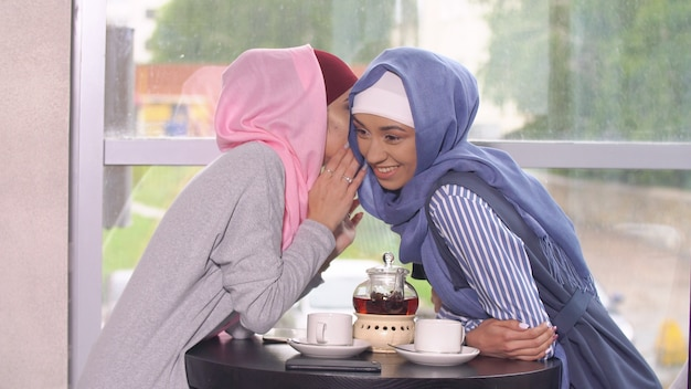 Two beautiful muslim business girls in cafe.