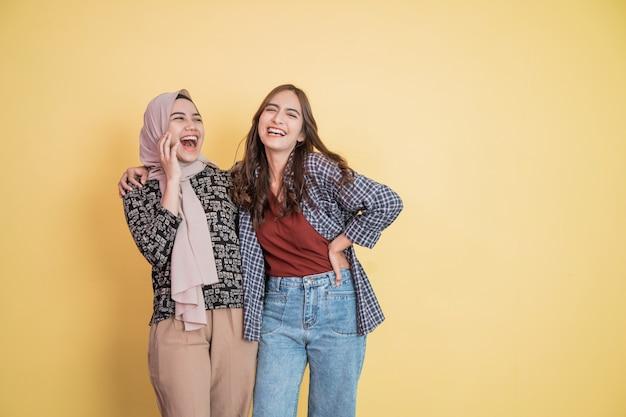 두 명의 아름다운 이슬람 여성이 카피스페이스를 들고 어깨에 손을 얹고 웃고 농담을 한다