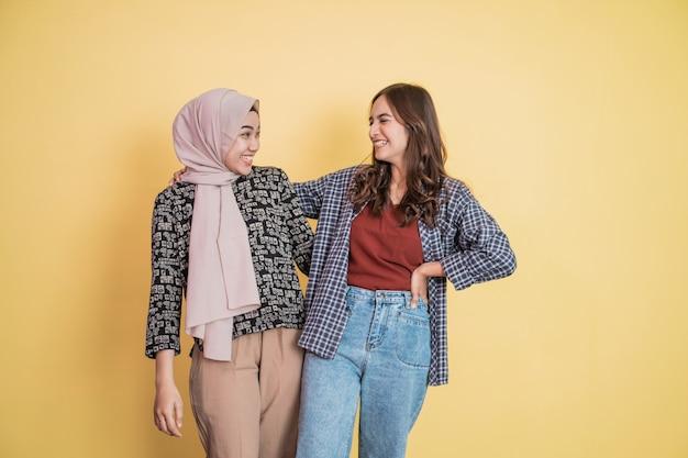 두 명의 아름다운 이슬람 여성이 카피스페이스를 들고 어깨에 손을 얹고 수다를 떨면서 웃고 있다