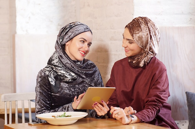 Two beautiful muslim women sitting in a cafe and using a tablet