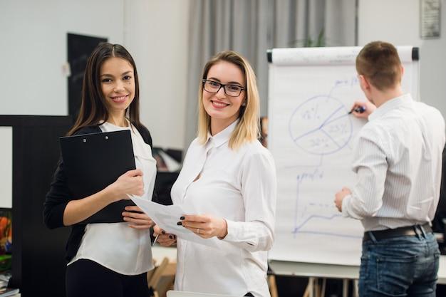 男の同僚がフリップチャートにビジネス戦略を描いている間に会話をしている2つの美しいオフィスワーカー。