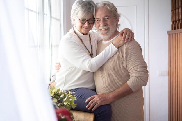 창 앞에서 사랑으로 서로 포옹하는 두 명의 아름다운 노인. 수석 부부 사이의 사랑과 행복의 개념